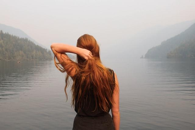 Dziewczyna z długimi rudymi włosami, podziwiająca widok.