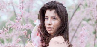Dziewczyna z ciemnymi włosami stojąca wśród różowych kwiatów