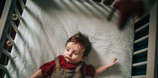 Chłopiec leżący w łóżeczku