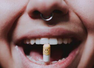Dziewczyna trzymająca antybiotyk między zębami