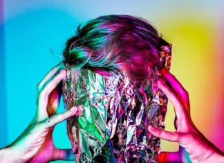 chłopak z folią na twarzy na kolorowym tle