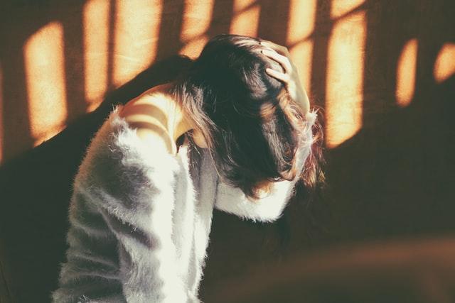 Dziewczyna trzymająca się za głowę z bólu