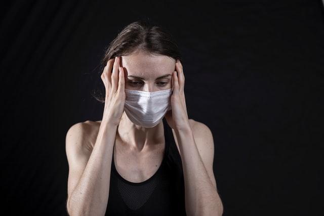 Chora dziewczyna w masce na czarnym tle