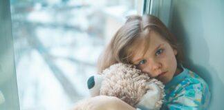 Chora dziewczynka przytulająca misia