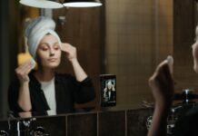Dziewczyna z ręcznikiem na głowie, zmywająca wacikiem makijaż