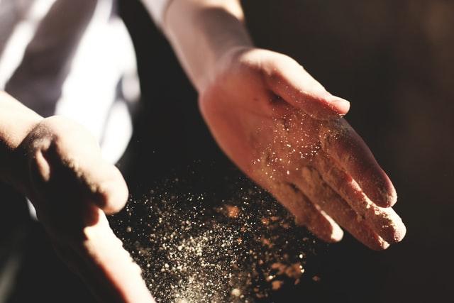 Dłonie przesypujące mąkę i drożdże
