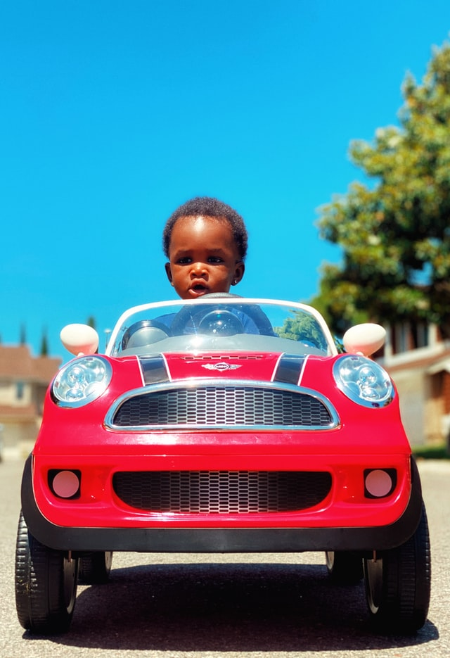 Małe dziecko w czerwonym, dziecięcym aucie