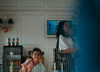 Dziecko w hotelowej recepcji i torba podróżna