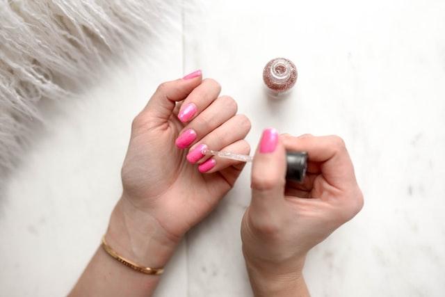 Dziewczyna malująca paznokcie na różowo
