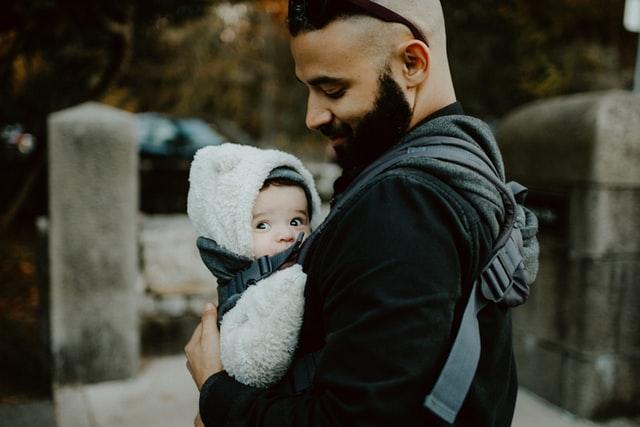 Tata noszący dziecko z przodu w nosidle