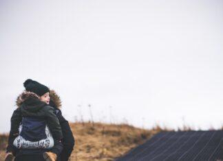 Mama nosząca dziecko na plecach w nosidle