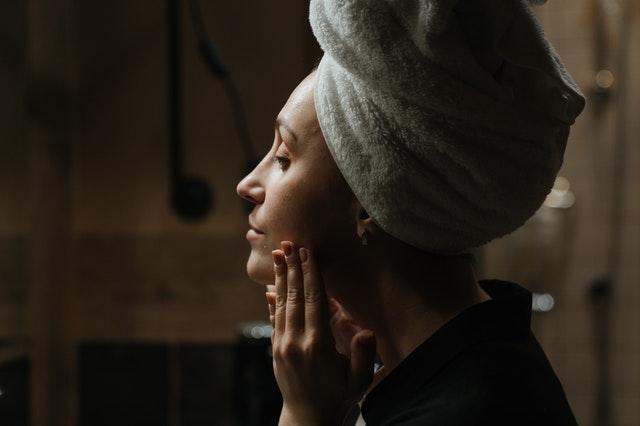 Dziewczyna w ręczniku na głowie, wklepująca kosmetyk w skórę twarzy