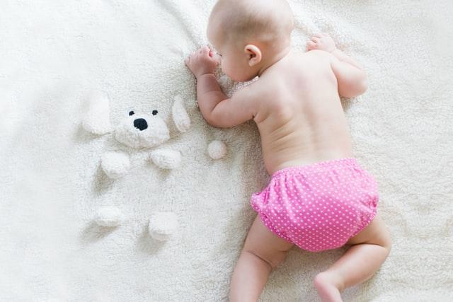Mała dziewczynka w pieluszce wielokrotnego użytku i miś