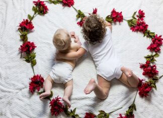 Dwoje dzieci w w pieluszkach wielokrotnego użytku leżące w sercu z kwiatów
