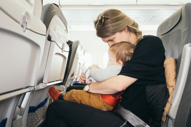 Mama z malutkim dzieckiem na kolanach lecąca samolotem.