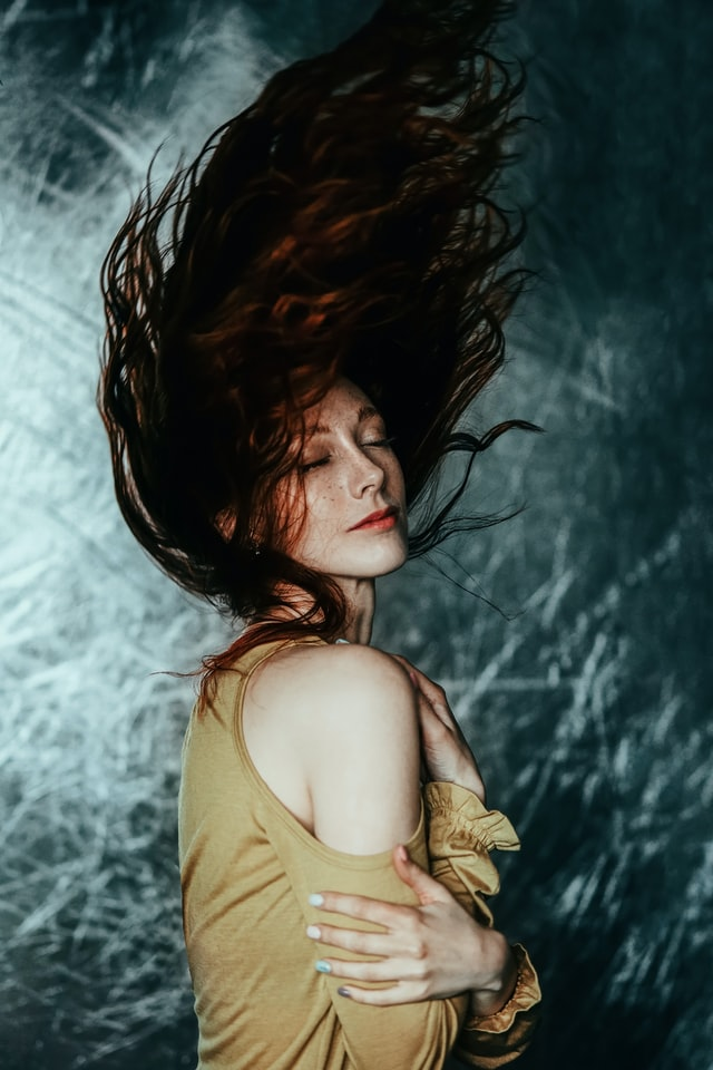 Dziewczyna machająca długimi, rudymi, włosami