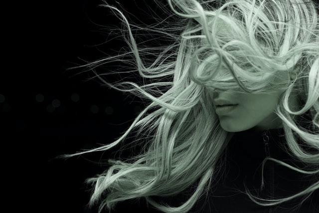 Blondynka machająca włosami na czarnym tle