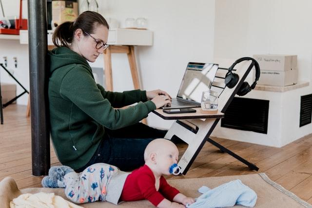 Mama pracująca przy komputerze z małym dzieckiem na kolanach