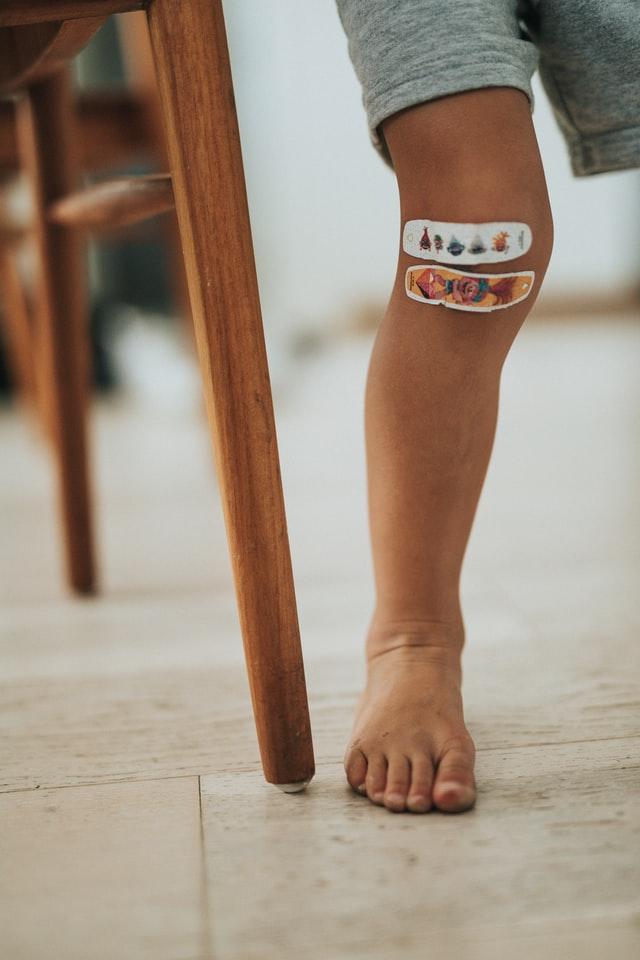 Nóżka dziecka z dwoma kolorowymi plastrami.