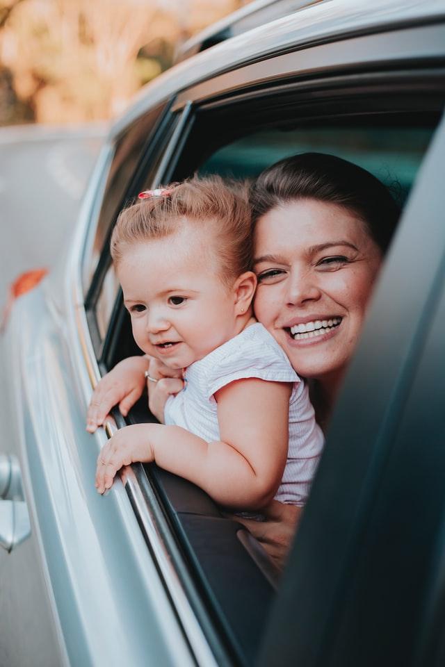 Mama i dziecko wyglądające przez okno samochodu.