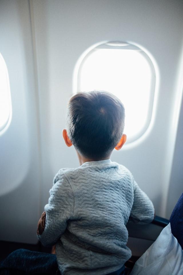 Dziecko patrzące przez okienko w samolocie.