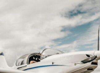 Mały chłopiec siedzący na pasie startowym, w tle samolot.