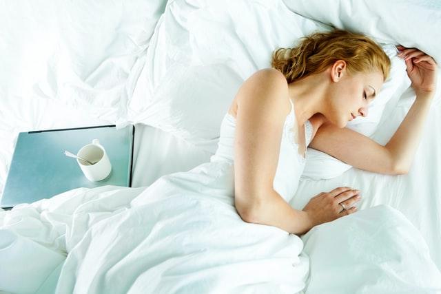 Dziewczyna śpiąca w łóżku a obok niej laptopp