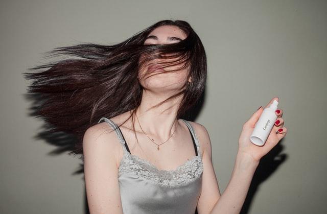 Dziewczyna z ciemnymi, długimi włosami, trzymajaca w ręce kosmetyk do pielęgnacji