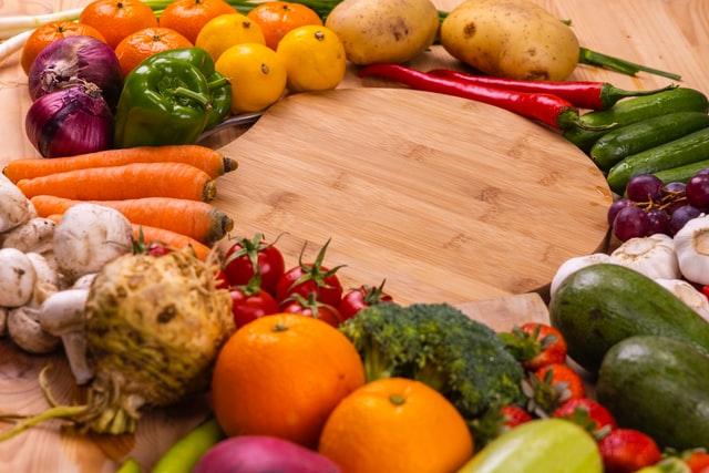 Deska pełna kolorowych warzyw i owoców.